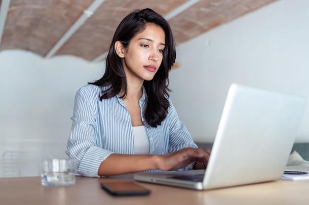 Foto de mulher de negócios jovem elegante trabalhando com seu laptop no escritório.