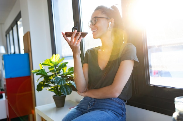 Foto de mulher de negócios jovem sorridente usando as mãos livres para fazer uma chamada com o celular enquanto está sentado ao lado da janela no escritório.