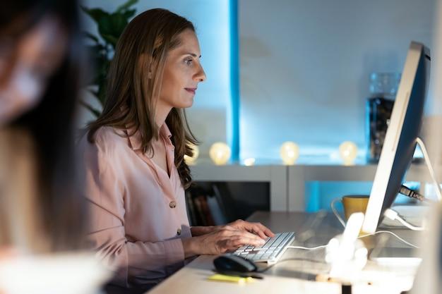 Foto de mulher de negócios maduros concentrada, trabalhando com seu computador no escritório.