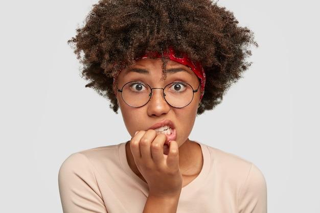 Foto de mulher de pele escura envergonhada olhando ansiosa, roendo as unhas