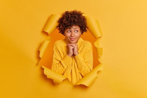 Foto de mulher de pele escura satisfeita mantendo as mãos sob o queixo e olhando pensativamente para longe