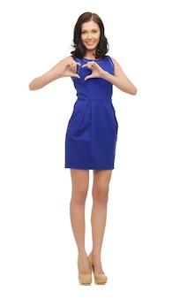Foto de mulher de vestido azul mostrando formato de coração