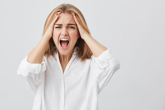 Foto de mulher decepcionada com cabelo loiro, segurando as mãos nos templos, rosto franzido, tendo a boca aberta gritando de desespero e terror.