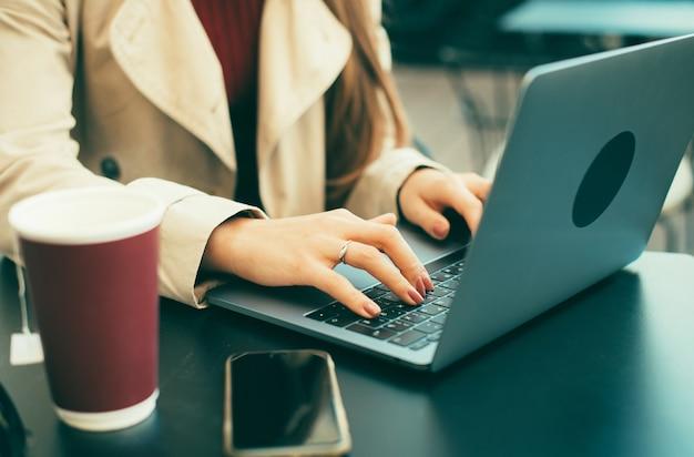 Foto de mulher digitando no computador em uma mesa em um café