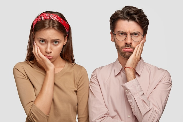 Foto de mulher e homem descontentes com expressões carrancudas