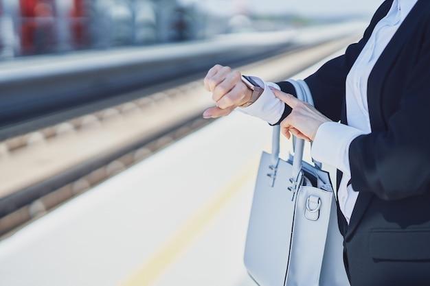 Foto de mulher elegante usando máscara de proteção andando com bolsa e mala na estação ferroviária