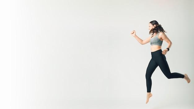 Foto de mulher em roupas esportivas pulando sobre um fundo branco com copyspace