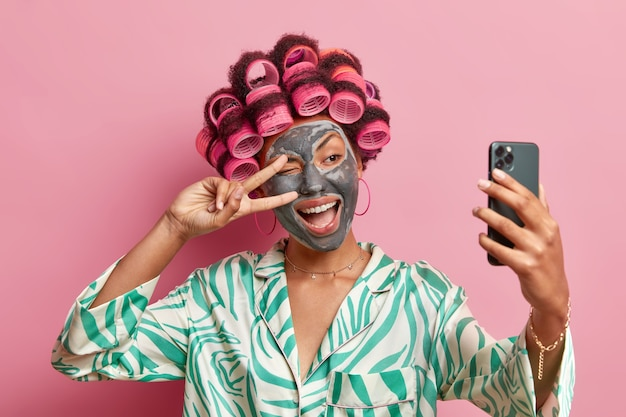 Foto de mulher étnica satisfeita faz gesto de paz sobre o olho sorri amplamente aplica beleza máscara rolos de cabelo tira retrato de selfie no celular usa roupão isolado sobre parede rosa