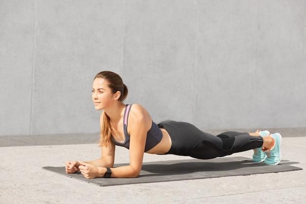 Foto de mulher faz exercício estático de prancha