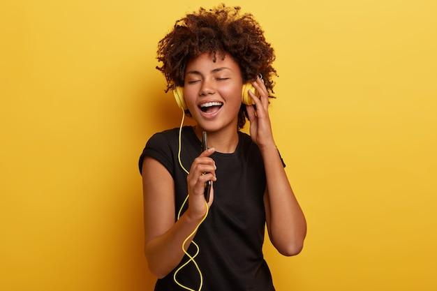 Foto de mulher feliz com a pele escura curtindo o final do dia feliz, ouve música alegre nos fones de ouvido, segura o telefone e fecha os olhos, da cintura para cima