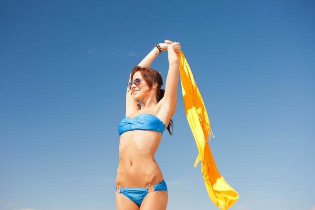 Foto de mulher feliz com sarongue amarelo na praia.