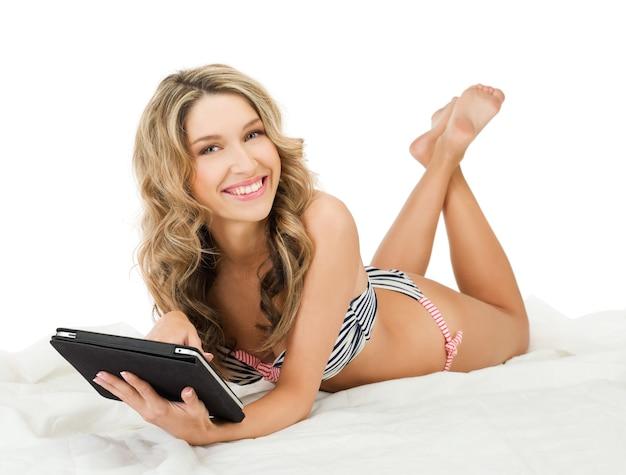 Foto de mulher feliz de biquíni com computador tablet pc
