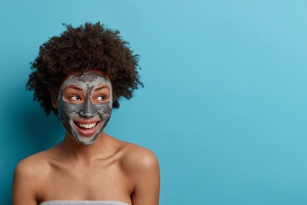 Foto de mulher feliz e satisfeita desvia o olhar com sorriso dentuço, faz procedimentos cosméticos em casa, aplica máscara de argila para cuidar da pele, mostra ombros nus, tem corpo bem cuidado. espaço em branco para o seu texto
