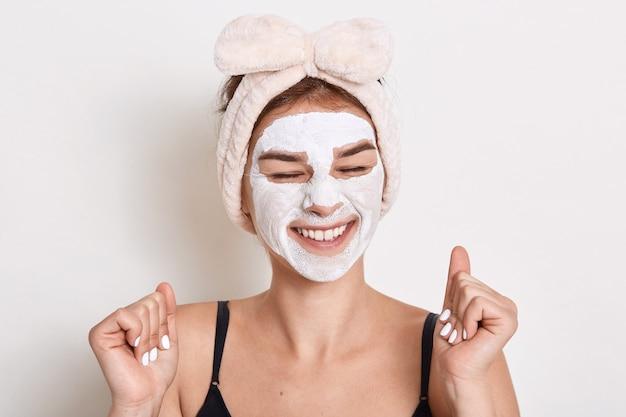 Foto de mulher feliz e satisfeita mantém os olhos fechados com um sorriso dentuço, faz procedimentos cosméticos em casa, aplica máscara de argila para cuidar da pele, fazendo manipulação anti-envelhecimento.