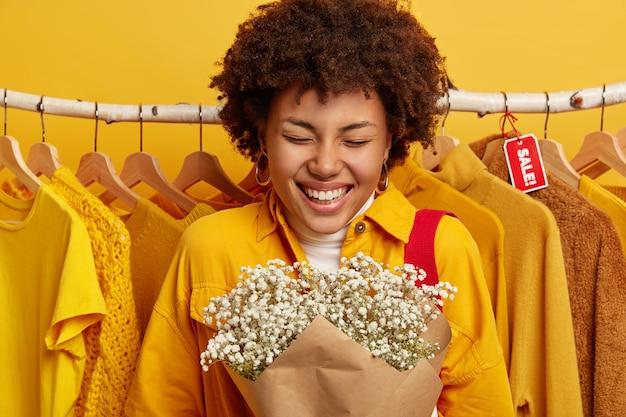 Foto de mulher feliz segurando um buquê, vestindo uma elegante jaqueta amarela, sorrindo amplamente, regozijando-se, perto de roupas em cabides