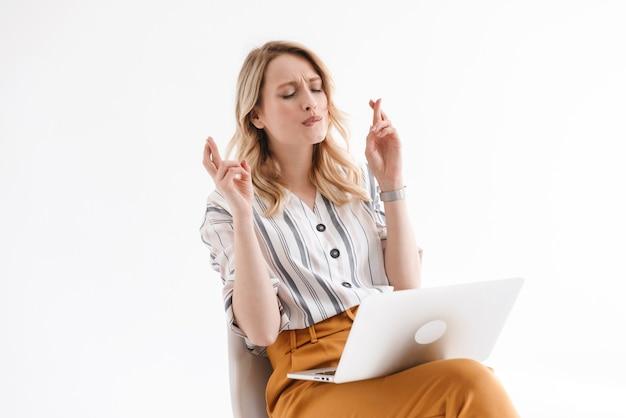 Foto de mulher focada na europa vestindo roupas casuais usando laptop e cruzando os dedos enquanto está sentada na cadeira isolada sobre a parede branca