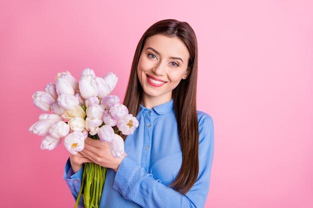 Foto de mulher fofa e feliz segurando um monte de tulipas brancas frescas grandes nas mãos