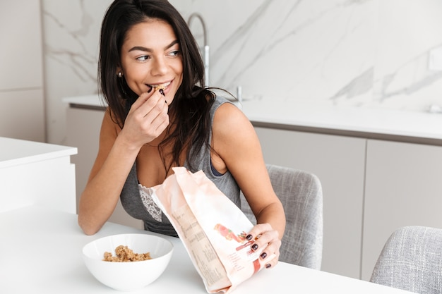 Foto de mulher fresca feliz tomando café da manhã e comendo granola de manhã, em casa interior