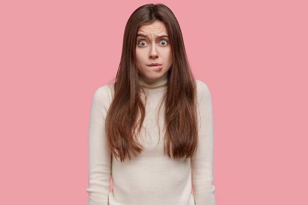 Foto de mulher frustrada e preocupada com a cintura para cima morde o lábio inferior, parece confusa, preocupada com algo