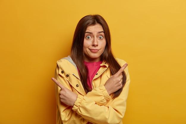 Foto de mulher hesitante inconsciente com cabelos escuros aponta para o lado, escolhe entre duas opções, tem expressão facial de surpresa, usa paletó, posa contra parede amarela, diz melhor olhar