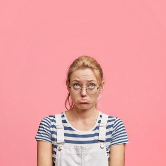 Foto de mulher infeliz e descontente olhando desesperadamente para cima