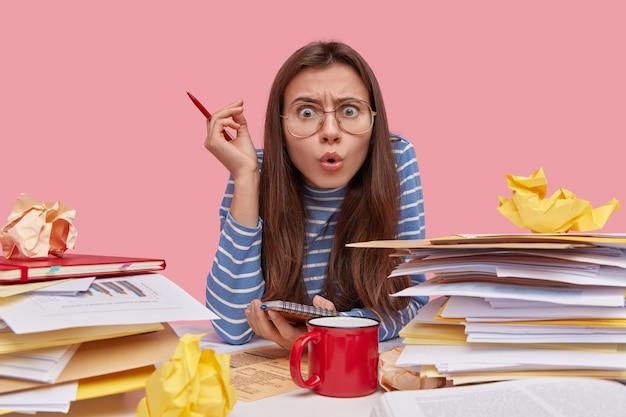 Foto de mulher insatisfeita com expressão de medo, olha com espanto, segura caneta na mão, tem expressão de espanto, trabalha com documentação