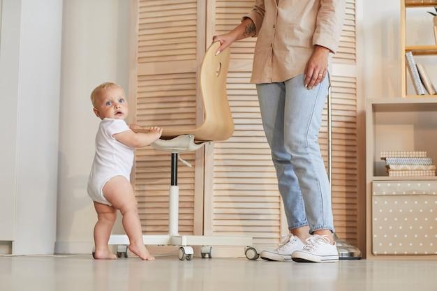 Foto de mulher irreconhecível vestindo roupa casual, ajudando seu filho a aprender a ficar de pé e andar