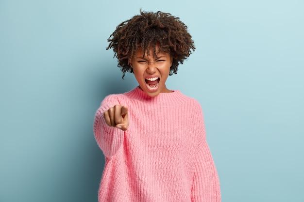 Foto de mulher irritada com cabelo encaracolado, aponta diretamente para a câmera e grita aborrecida
