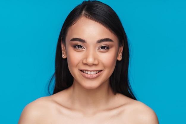 Foto de mulher jovem asiática otimista posando isolada na parede azul.