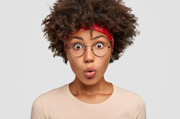 Foto de mulher jovem assustada com a respiração suspensa, olhos abertos, olhares maravilhados