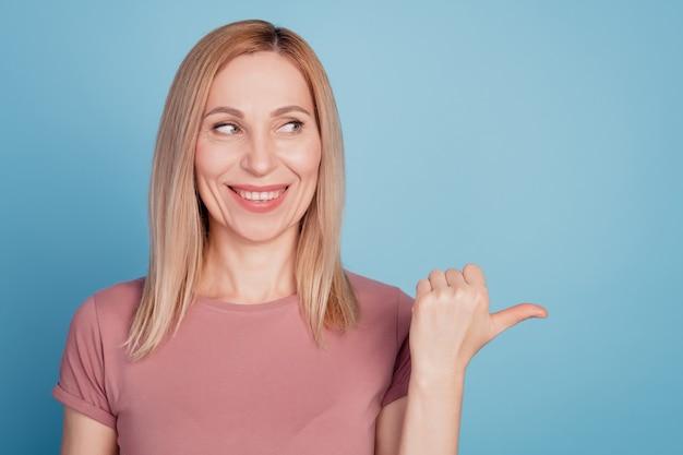 Foto de mulher jovem com sorriso positivo e feliz com aparência de indicador de espaço vazio e conselho promocional isolado sobre fundo de cor azul