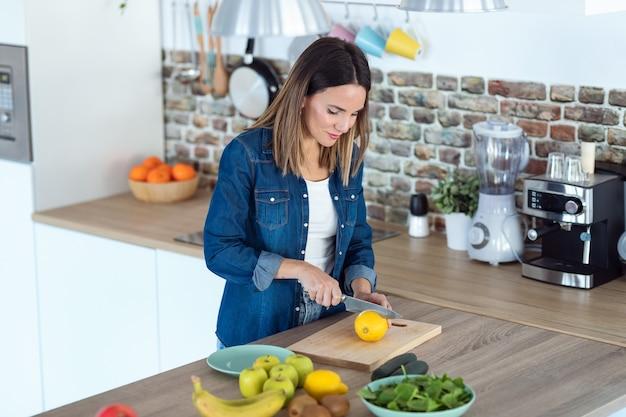 Foto de mulher jovem, cortando limões para preparar bebida de desintoxicação na cozinha em casa.