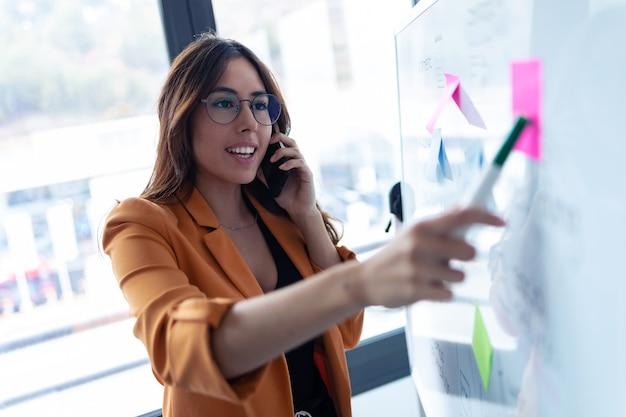 Foto de mulher jovem de negócios falando no celular enquanto trabalhava no quadro branco com adesivos de post-it no escritório.
