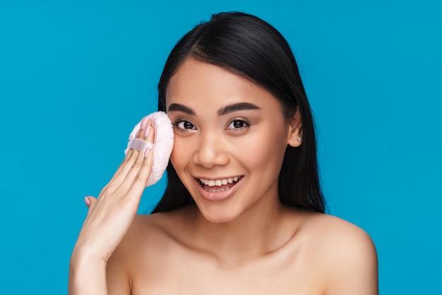 Foto de mulher jovem e alegre asiática posando isolada na parede azul, segurando o sopro de pó.