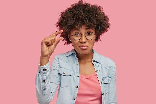 Foto de mulher jovem e atraente com corte de cabelo afro mostra algo muito pequeno ou minúsculo, gesticula com a mão, tem pele morena, vestida com jaqueta jeans, isolada sobre parede rosa. é muito pequeno