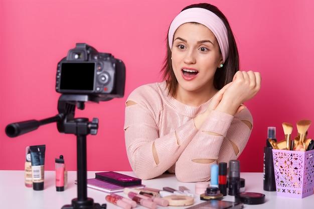 Foto de mulher jovem e atraente morena rodeada por novos produtos de beleza