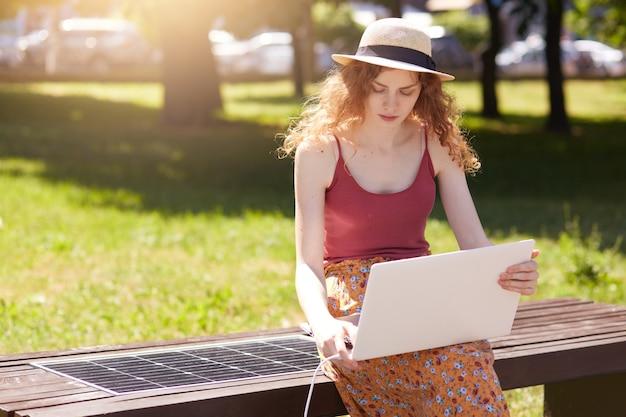 Foto de mulher jovem e atraente, trabalhando com o laptop ao ar livre, carregando o dispositivo no banco inovador, construído na porta usb