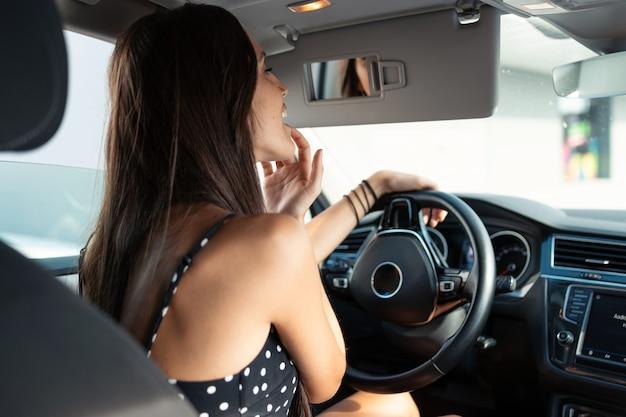 Foto de mulher jovem e bonita aplicando protetor labial enquanto olha no espelho retrovisor do carro.