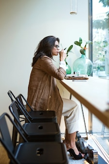 Foto de mulher jovem e bonita bebendo chá verde matcha com leite na mesa de madeira no café.