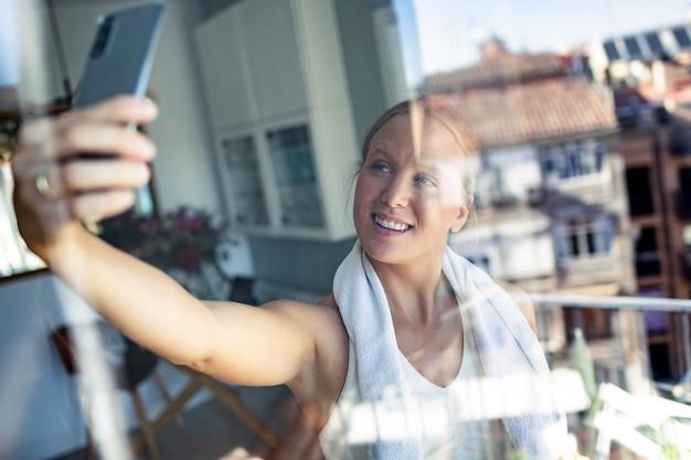 Foto de mulher jovem e desportiva tirando uma selfie com seu telefone inteligente enquanto faz uma pausa no exercício na sala de estar em casa.
