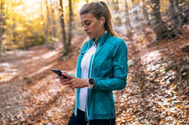 Foto de mulher jovem e desportiva usando seu telefone celular enquanto relaxa depois de correr no parque na manhã de outono.