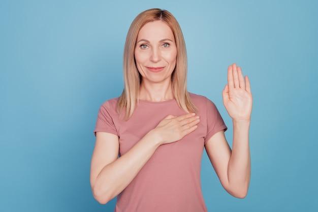 Foto de mulher jovem e séria com a mão no peito prometendo contar a verdade isolada em um fundo de cor azul