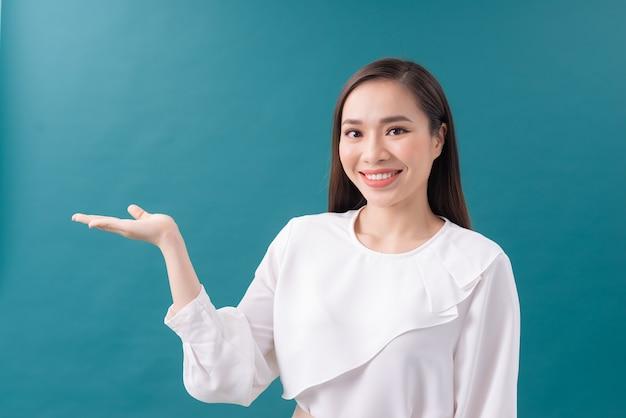 Foto de mulher jovem feliz em pé isolada sobre o fundo da parede azul. olhando a câmera mostrando o copyspace