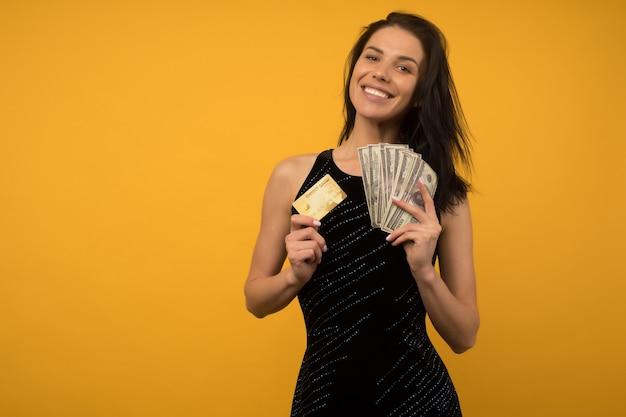 Foto de mulher jovem feliz satisfeito posando isolado sobre o fundo da parede amarela, segurando dinheiro e cartão de crédito ou dívida.