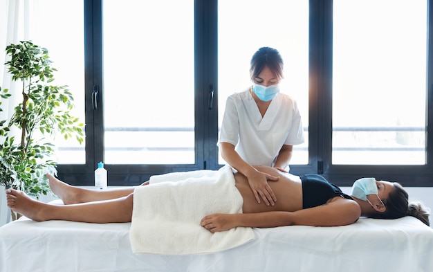 Foto de mulher jovem fisioterapeuta massageando a barriga na mulher grávida em uma maca em casa. mulheres usando máscara cirúrgica e novo conceito normal.