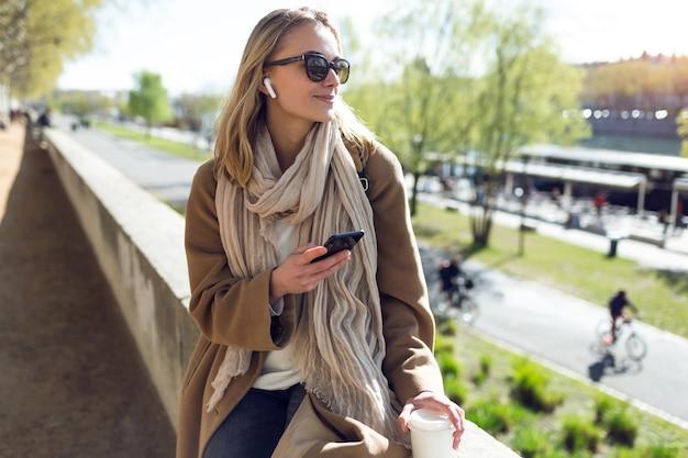 Foto de mulher jovem, ouvindo música com fones de ouvido sem fio e o smartphone na rua.