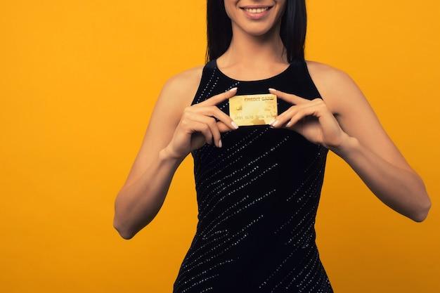 Foto de mulher jovem satisfeita posando isolada sobre o fundo da parede amarela, segurando um cartão de débito ou crédito.