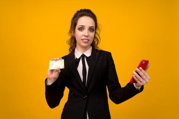 Foto de mulher jovem satisfeita posando isolada sobre o fundo da parede amarela, usando o telefone móvel, segurando o cartão de débito.