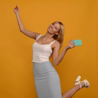 Foto de mulher jovem satisfeita posando isolada sobre o fundo da parede amarela, usando telefone celular.
