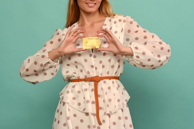 Foto de mulher jovem satisfeita posando isolada sobre o fundo da parede azul, segurando um cartão de débito ou crédito.